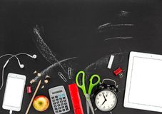 Back to school Office supplies digital gadgets chalkboard. Back to school. Office supplies and digital gadgets on black chalkboard background Royalty Free Stock Images