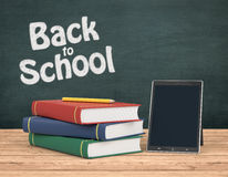Back to school. One tablet pc on a wooden desk, a stack of book and a chalkboard on background with text: back to school 3d render Stock Photo