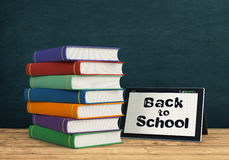 Back to school. One tablet pc on a wooden text, a stack of book at the right and a chalkboard on background, empty space at the right of the image  (3d render Stock Photography