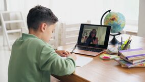 Back to School, Online learning, distance lesson, education at home, technology for kids. Caucasian boy with textbooks