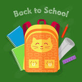 Back to School. Orange Bag on Green Background. Back to school. Orange-yellow bag with smiled cat and two pockets on green background. Behind bag green and blue Stock Photography