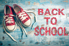 Back to school. Pair of child sneakers on wooden background with back to school sign Stock Images
