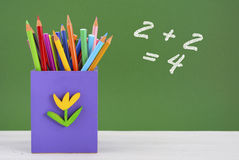 Back to school pencil box against green chalkboard. Royalty Free Stock Images