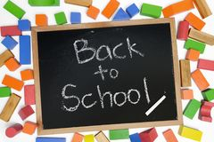 Back to School phrase on blackboard. Surrounded by wood blocks toy Stock Photos