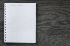 Back to school phrase in notepad with chequered. Pages on gray wood table, top view Royalty Free Stock Photo