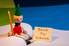 Back to school. A Pinocchio puppet sitting on a notebook next to a note with the words Back to school written on it Stock Images