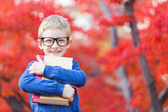 Back to school. Portrait of smart little boy in glasses holding book ready for school in beautiful autumn park Stock Photos
