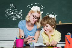 Back to school. Preschooler. School and kid concept. Mother teaching her son in classroom at school. royalty free stock photos