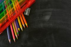 Back to school. Rainbow pencil case with school supplies for student. Black background. Copy space stock images