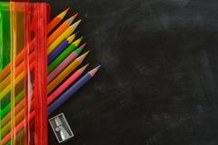 Back to school. Rainbow pencil case with school supplies for student. Black background. Copy space