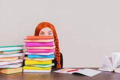 Back to school. Redhead schoolgirl peeks out the books on a gray background. A surprised girl is going to school. Surprised face. Stock Photo