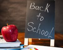 Back to school reminder with apple. Back to school reminder for teachers and students with apple, notepad, textbooks, pencils and textbooks Royalty Free Stock Photo