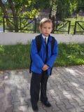 Back to school. Sad schoolboy in school uniform and backpack standing otdoor Stock Images