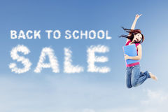Back to school sale concept. Text of back to school sale with female college student jumps on the side of text Stock Images