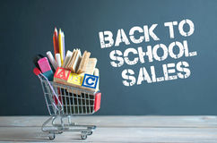 Back to school sales. Shopping cart filled with stationery merchandise against chalkboard with sales sign Stock Photos