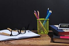 Back to school scenery. Stationery of campus student are on the table in front of a black board Royalty Free Stock Photography