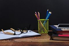 Back to school scenery. Stationery of campus student are on the table in front of a black board Stock Photography