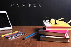 Back to school scenery. Scenery of stationery for school and campus on a table in front of a black board Royalty Free Stock Images