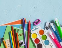 Back to school. School accessories - notebooks, pens, pencils, paint on a blue background, top view. Education concept. Flat lay stock images