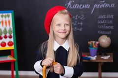 Back to school! A schoolgirl stands at the blackboard with a ruler. A schoolgirl answers the lesson. A first-grader near a chalk b royalty free stock photo
