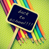 Back to school. Sentence back to school written in a blackboard label and some pencil crayons of different colors in a green background, with a retro effect Royalty Free Stock Image