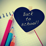 Back to school. Sentence back to school written in a heart-shaped blackboard and some pencil crayons of different colors on a notebook, with a retro effect Royalty Free Stock Photography