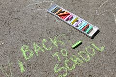 Back to school sigh written with colored chalks on a pavement. Drawing Back to school on an asphalt. and vacation concept. Education concept. School and fun Royalty Free Stock Photography