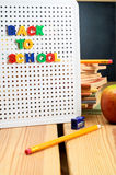Back To School Sign. A letterboard on wooden planked table with the words 'back to school' displayed, surrounded by classroom items with a blackboard in the far royalty free stock photography