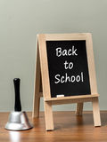 Back to school. Silver handbell and blackboard with Back to School phrase placed on brown desktop over green wall Stock Images