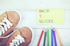 Back to School. Slippers and colored pencils on a wooden table Royalty Free Stock Image