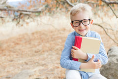 Back to school. Smart excited little boy in glasses studying with book ready for school, back to school concept Royalty Free Stock Photo