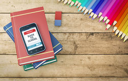 Back to school. Smartphone with a reminder app with text: back to school, with books and pencils, wooden background 3d render Stock Photo
