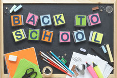 Back to School. Some cube letters composing the words BACK TO SCHOOL on a blackboard. Some school materials representing the start of a new educational course Royalty Free Stock Images