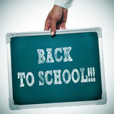 Back to school. Someone holding a chalkboard with the sentence back to school written in it Stock Photos