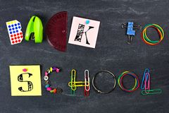 BACK TO SCHOOL spelled with school supplies against blackboard Stock Photo