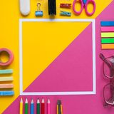 Square frame with stationery on pink and yellow background. flat lay. Royalty Free Stock Image