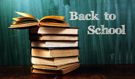 Back to school. Stack of books in front of   green  blackboard .Warm tones Stock Photos