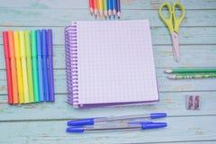 School supplies. Color pencils,note book, blue pens, sciccors, markers, glue, pencil sharpener, clips stock photo