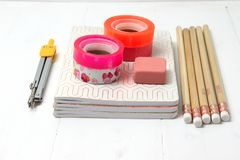 Basic stationery - notebooks, pencils, tapes, compass, gum stock image