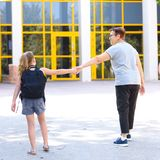 Back to school struggle after summer vacation. Grandma dragging an anxious kid to school. royalty free stock photography