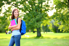 Back to school student girl looking to side. In park holding books and note books wearing backpack. Female university college student looking at copyspace in Royalty Free Stock Photos