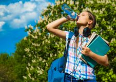 Back to school student teenager girl drinks water from a bottle and holding books and note books wearing backpack. Outdoor in park with copy space Stock Photo