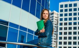 Student teenager girl holding books and note books. Outdoor portrait of young teenager brunette girl with long hair. Glass buildin royalty free stock image
