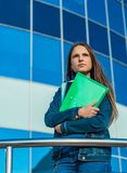Student teenager girl holding books and note books. Outdoor portrait of young teenager brunette girl with long hair. Glass buildin stock photo
