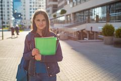 Back to school student teenager girl holding books and note books wearing backpack. Outdoor portrait of young teenager brunette gi stock images