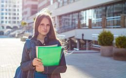 Back to school student teenager girl holding books and note books wearing backpack. Outdoor portrait of young teenager brunette gi royalty free stock images