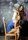 Back to school after summer vacations, two teen girls in classroom with blackboard painted together Royalty Free Stock Photo
