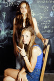 Back to school after summer vacations, two teen girls in classroom with blackboard painted together Royalty Free Stock Image