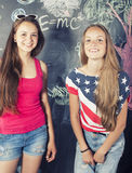 Back to school after summer vacations, two teen real girls in classroom with blackboard painted together Royalty Free Stock Photo