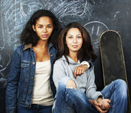 Back to school after summer vacations, two teen real girls in classroom with blackboard painted together, lifestyle. Mixed races people concept close up Stock Photography
